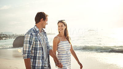 Buy stock photo Shot of a smiling mature couple walking hand in hand together at the beach at sunset