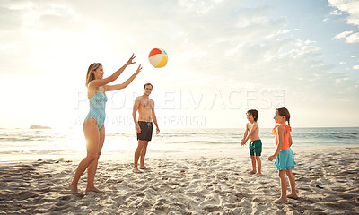 Buy stock photo Shot of a family playing catch with a beach ball while enjoying a day at the beach