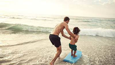 Buy stock photo Shot of a father teaching his little son how to wakeboard at the beach in the late afternoon
