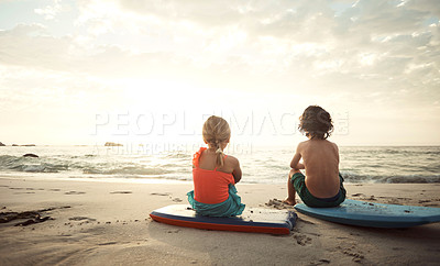 Buy stock photo Shot of a little brother and sister sitting on wakeboards on the beach watch the sunset in the late afternoon