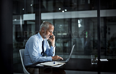 Buy stock photo Shot of a mature businessman using his laptop and phone at work
