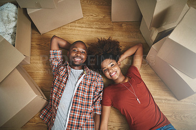 Buy stock photo High angle shot of a young couple taking a break while moving into their new home