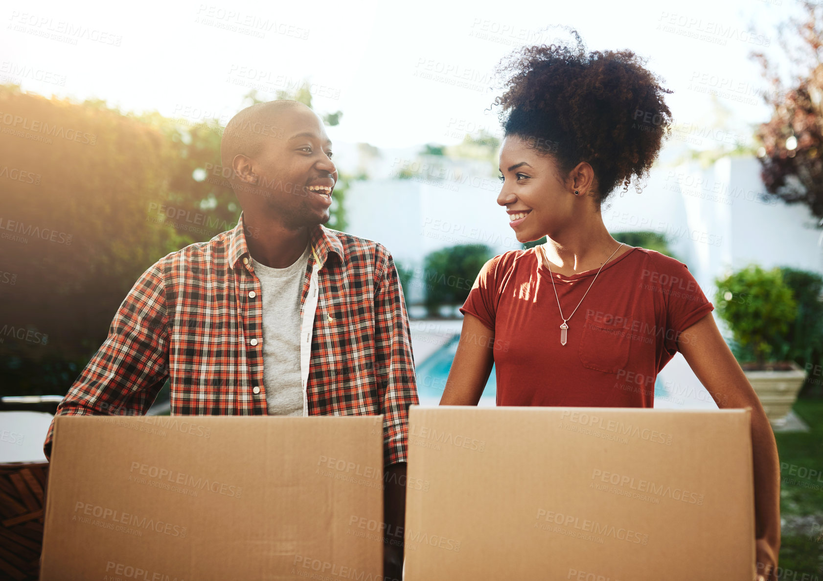 Buy stock photo Cropped shot of a young couple carrying boxes while moving into their new home