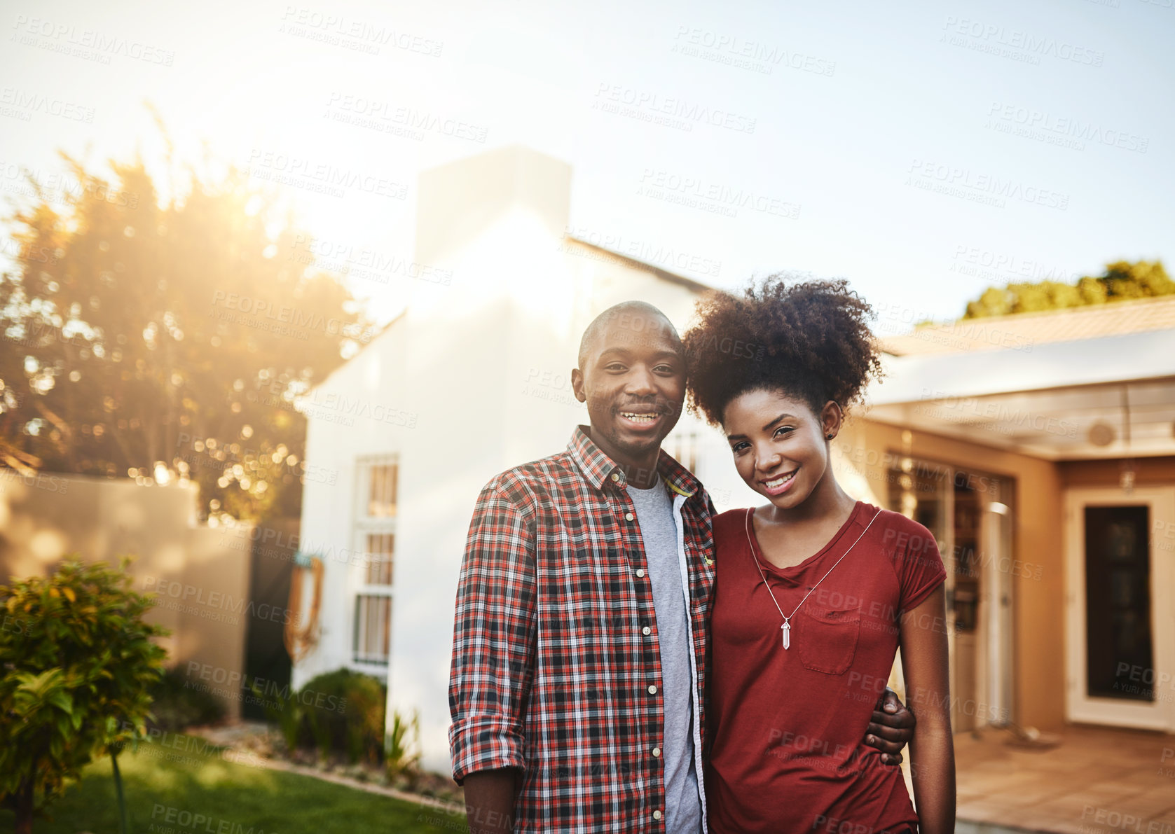 Buy stock photo Portrait of a young couple standing outside in front of their new house