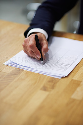 Buy stock photo Closeup shot of a businessman sitting at a table in an office going through a checklist