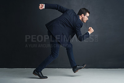 Buy stock photo Studio shot of a businessman running against a gray background