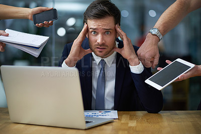 Buy stock photo Portrait of a stressed out looking businessman surrounded by demanding colleagues while sitting at a desk in an office