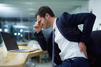 Buy stock photo Shot of a businessman wincing in pain and holding his lower back while sitting at a desk in an office