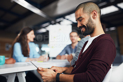 Buy stock photo Shot of a young man sitting at a table in an office using a digital tablet with colleagues working in the background