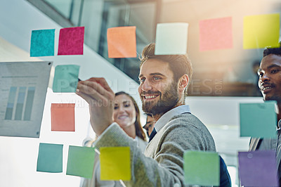 Buy stock photo Cropped shot of a group of businesspeople brainstorming with sticky notes on a glass wall in an office