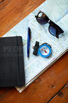 Buy stock photo Shot of a map and adventure gear arranged on a table