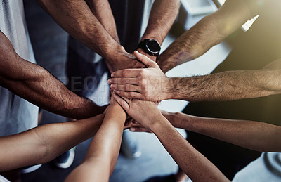 Buy stock photo Cropped shot of a group of fit people joining their hands in unity at the gym