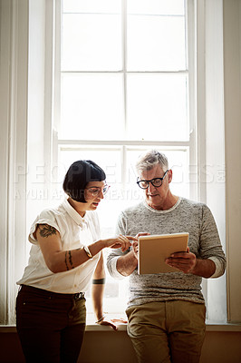 Buy stock photo Shot of two design colleagues using a tablet together in the office