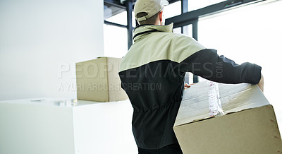 Buy stock photo Shot of an unidentifiable deliveryman carrying a large box