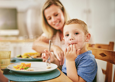 Buy stock photo Portrait of a happy little boy enjoying a meal with his mother at home