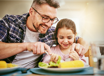Buy stock photo Shot of a happy father and daughter enjoying a meal together at home