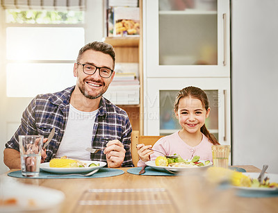 Buy stock photo Portrait of a happy father and daughter enjoying a meal together at home