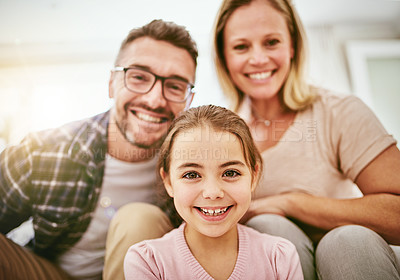 Buy stock photo Portrait of a happy young family posing in their living room at home