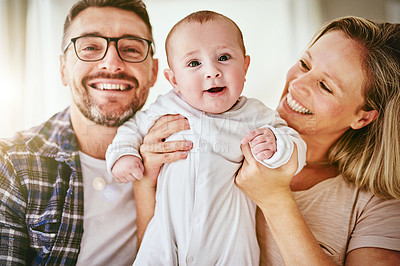 Buy stock photo Portrait of two happy parents posing with their baby boy at home