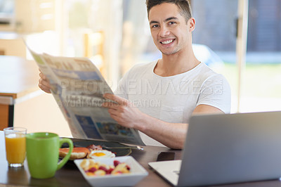 Buy stock photo Cropped shot of a young man reading the morning paper while having breakfast