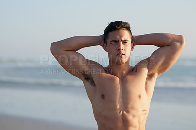 Buy stock photo Cropped portrait of a handsome young man standing with his hands behind his head at the beach