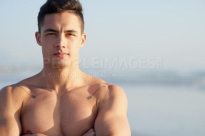 Buy stock photo Cropped portrait of a handsome young man standing with his arms folded at the beach