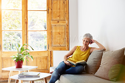 Buy stock photo Shot of a mature woman sitting on her sofa at home reading a book