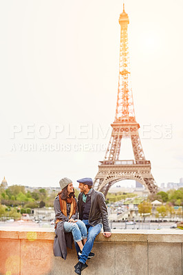 Buy stock photo Shot of a happy young couple sitting together in front of the Eiffel Tower