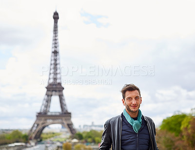 Buy stock photo Portrait of a smiling young man standing in front of the Eiffel Tower