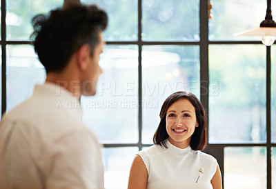 Buy stock photo Shot of a young couple talking together in their kitchen