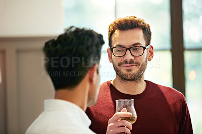 Buy stock photo Shot of two friends talking together and drinking wine while standing in the kitchen at home