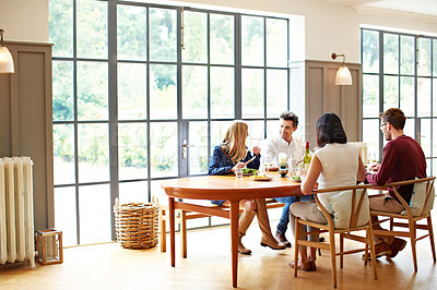 Buy stock photo Shot of a group of friends enjoying a home-cooked dinner together
