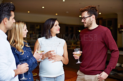 Buy stock photo Shot of a group of friends drinking wine and talking together at a get-together