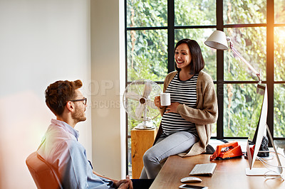 Buy stock photo Shot of a pregnant woman and her husband talking together in their home offic