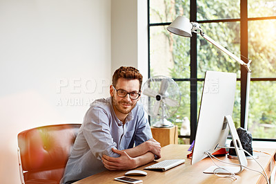 Buy stock photo Portrait of a smiling young man sitting at a desk in his home office