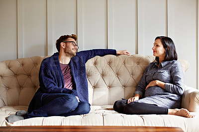 Buy stock photo Shot of a young expecting couple talking together while sitting on the sofa at home