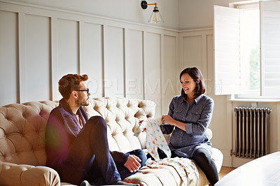 Buy stock photo Shot of a young pregnant woman showing her husband baby clothing while sitting on their sofa