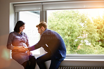 Buy stock photo Shot of a man touching his pregnant wife's stomach while sitting on a window sill at home