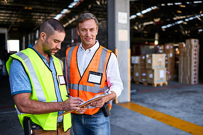 Buy stock photo Shot of two workers talking together over a clipboard while standing at the entrance of a warehouse