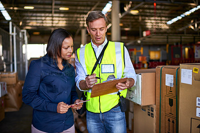 Buy stock photo Shot of two warehouse workers using a digital tablet and looking at paperwork