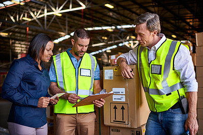 Buy stock photo Shot of a group of coworkers reading paperwork while standing in a large warehouse