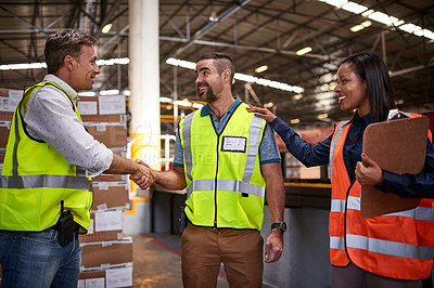 Buy stock photo Shot of two workers shaking hands together in a large warehouse while a coworker looks on