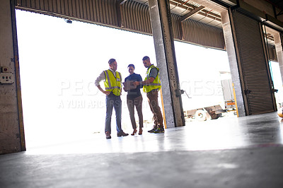 Buy stock photo Shot of three workers talking together inside the entrance to a large warehouse