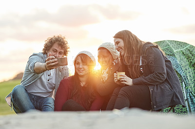 Buy stock photo Shot of a group of friends taking a selfie together while on a weekend camping trip