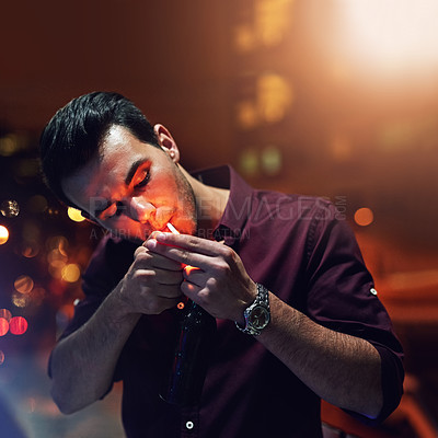 Buy stock photo Shot of a young man lighting a cigarette while standing in the balcony of a nightclub