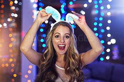 Buy stock photo Portrait of a happy young woman wearing a pair of bunny ears in a nightclub