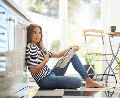 Buy stock photo Portrait of an attractive young woman chilling on her kitchen floor reading a newspaper