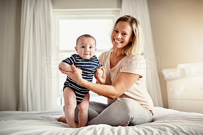 Buy stock photo Full length portrait of a mother sitting on a bed at home with her son
