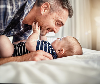 Buy stock photo Cropped shot of a father bonding with his son on a bed at home