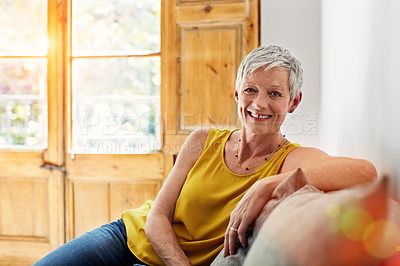 Buy stock photo Portrait of a smiling mature woman relaxing on her sofa at home